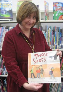 Laurie Collins holds the book that inspired the community service project in Newbury.