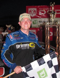 Eddie MacDonald with checkered flag in hand and trophy behind him.