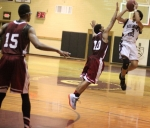 Kevin Scarlett (12 points) shoots over Kam Nobles