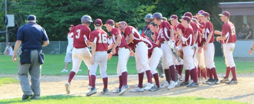 Connor Wile (#3) is met at home by his teammates in the fifth inning after a long home run.