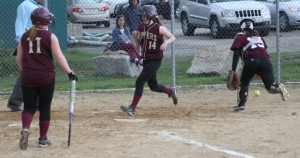 Molly Kelley steps on home as catcher Mollie Watson chases a bad throw