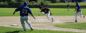 Third baseman Alex Ray chases a deflected ball as Drew Carter approaches third base.
