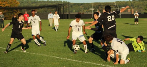 Bowdoin GK Jake Muscato (#23) is down and out as Nico Kaiafas (#9) has the ball at his feet