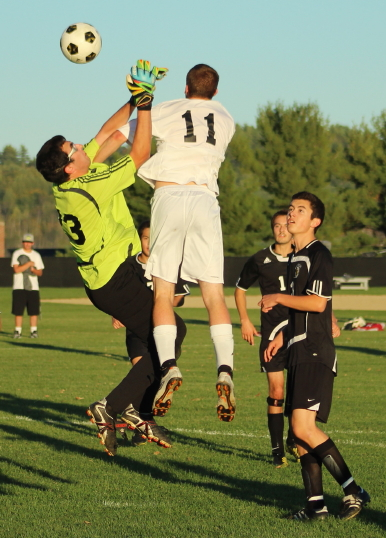 Eric Miller (#11) of Bridgton Academy contests a shot in front with Bowdoin GK Jake Muscato