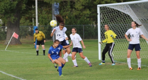 Orie Inirio heads out a Kennebunk corner kick over Sarah Thill