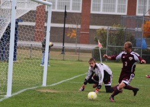 Ryder Bennell clears a ball away from in front of the Freeport net.