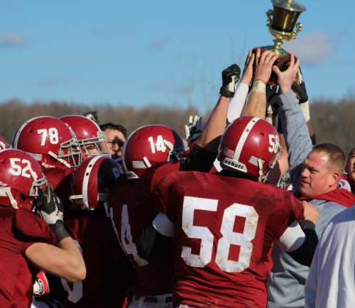 Bethel coach Jason Gill helps raise the Thanksgiving Day trophy for the Wildcats