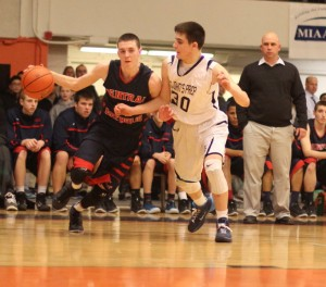Tyler Nelson drives on Max Burt (16 points) as CC coach Rick Nault watches