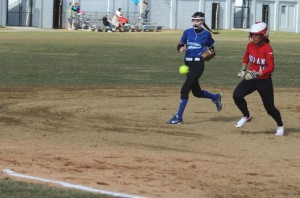 The throw from first goes past Alexi Boswell and shortstop Kylie Hayward