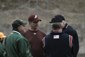 Frank Carey, Steve Malenfant, and the umpires meet after the ninth inning