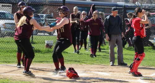 Celebrating begins as Shelby OBrien (#11) crosses home in the first inning