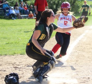 Catcher Sophia Warner waits for the throw as Sarah Webster prepares to slide in with the first Masco run