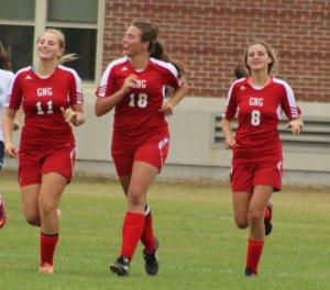 Izzy Detroy, Maria Valente, and Emma Woods celebrate a goal