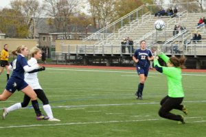 Jen Migliaccio pops the ball over the onrushing goalie Poli Tsiotos