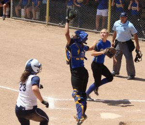 Catcher Hailey Perry jumps for a high throw as Cat Thompson nears the plate