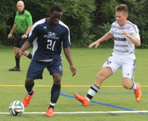 Hughes Bukunda shields the ball from Nathaniel Campbell