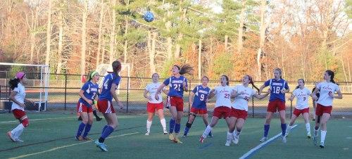 Eleven players follow a soccer ball