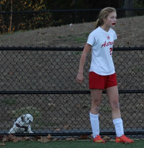 Courtney Velho lines up a corner kick in front of a canine spectator