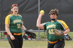 Pitcher Julia Perrone throws to first as teammate Cassidy looks on
