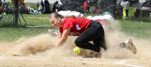 Amesbury pitcher Hayley Catania looks for the ball at home in a cloud of Jill Chelton dust