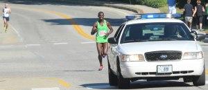 Moninda Marube follows the police car with Jim Johnson in the distance