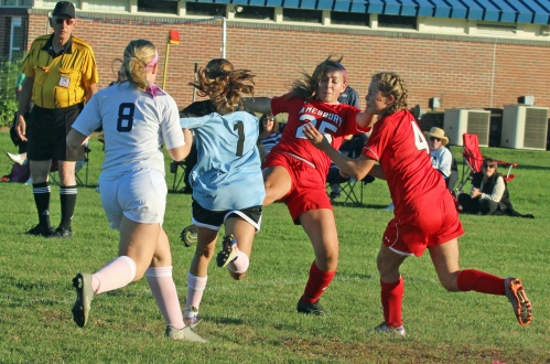 Emma Richardson (25) and Madison McGrath (4) challenge Triton keeper Dayna Rybicki