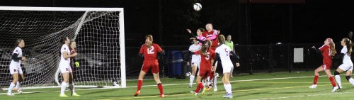 Haley Mignon (42) above the crowd looking to head in a corner kick.