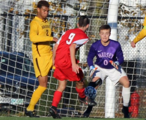 Abdel Talabi (#2) sticks a foot in front of Ben Lockhart's shot as Nauset GK Jack Avellar watches.