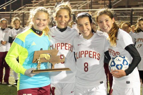 Newburyport captains Jen Stuart, Amelia Kroschwitz, Sami Kelleher, and Margaret Cote pose with the D3 North championship trophy