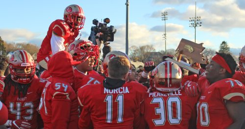 Everett players celebrate with the D1 Super Bowl trophy